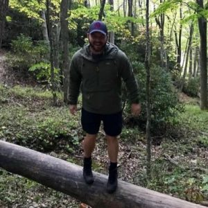 Greg Webb outdoors standing on a log